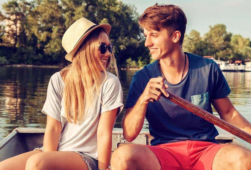 Young Couple Relaxing On A Boat Enjoying Sunny Day
