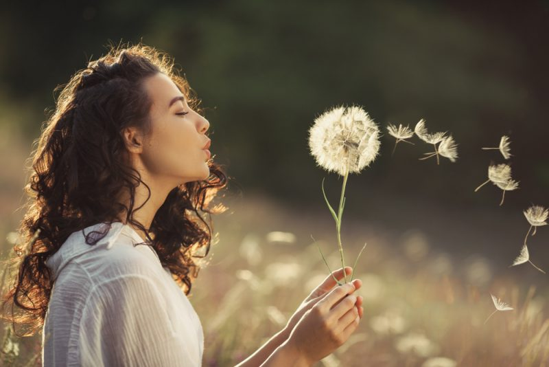 Young Woman sitting on the field in green grass and blowing dandelion