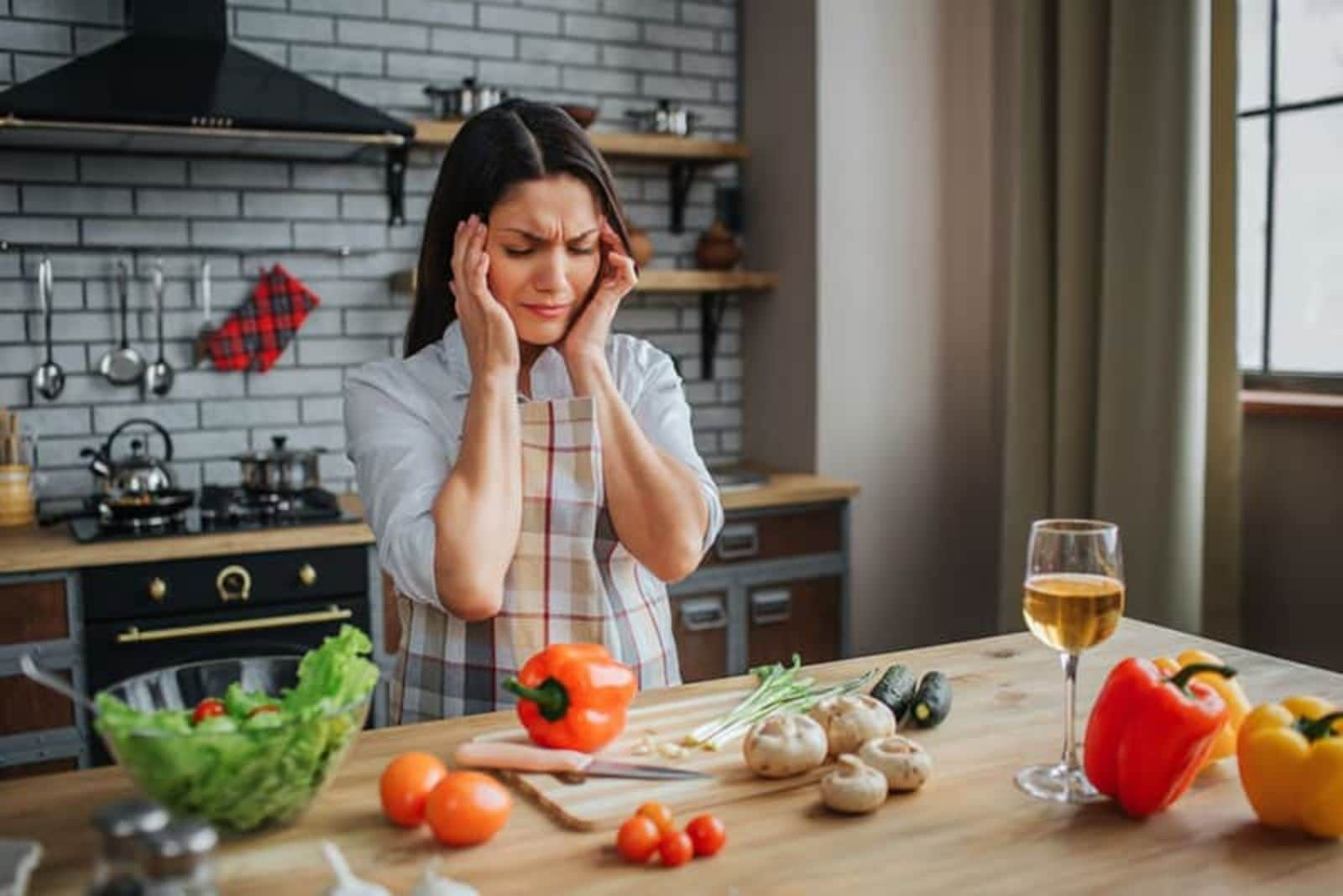 a confused woman stands in the kitchen
