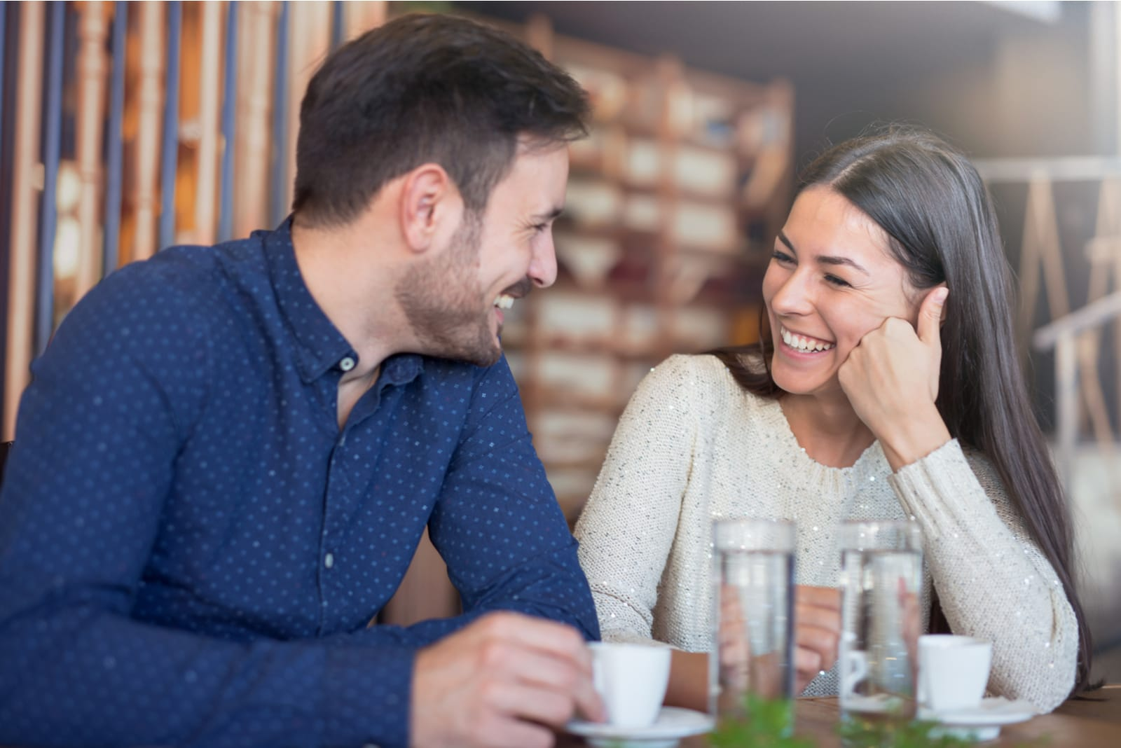 a couple in a cafe flirting and drinking coffee