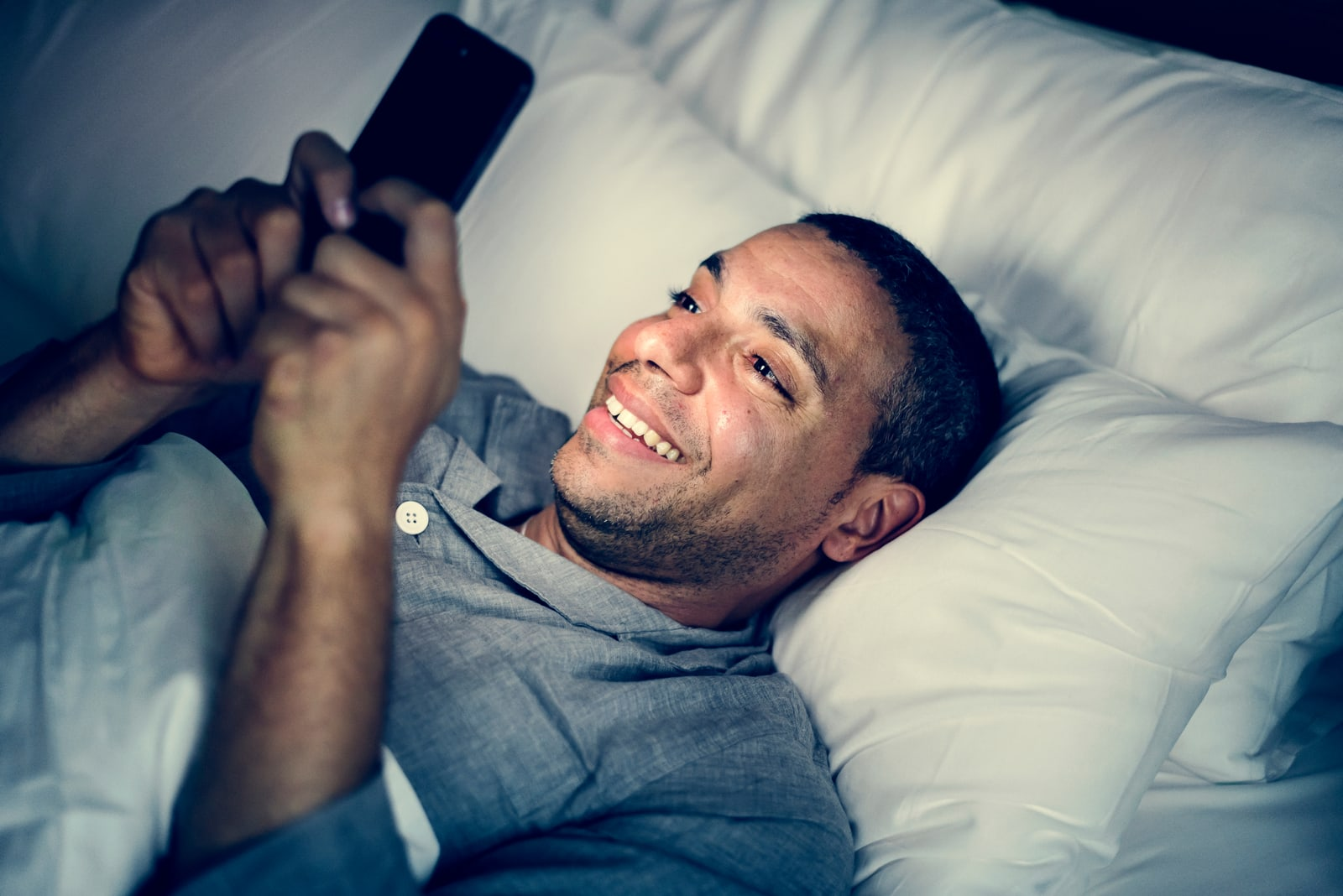 a happy man is lying in bed and using a smartphone