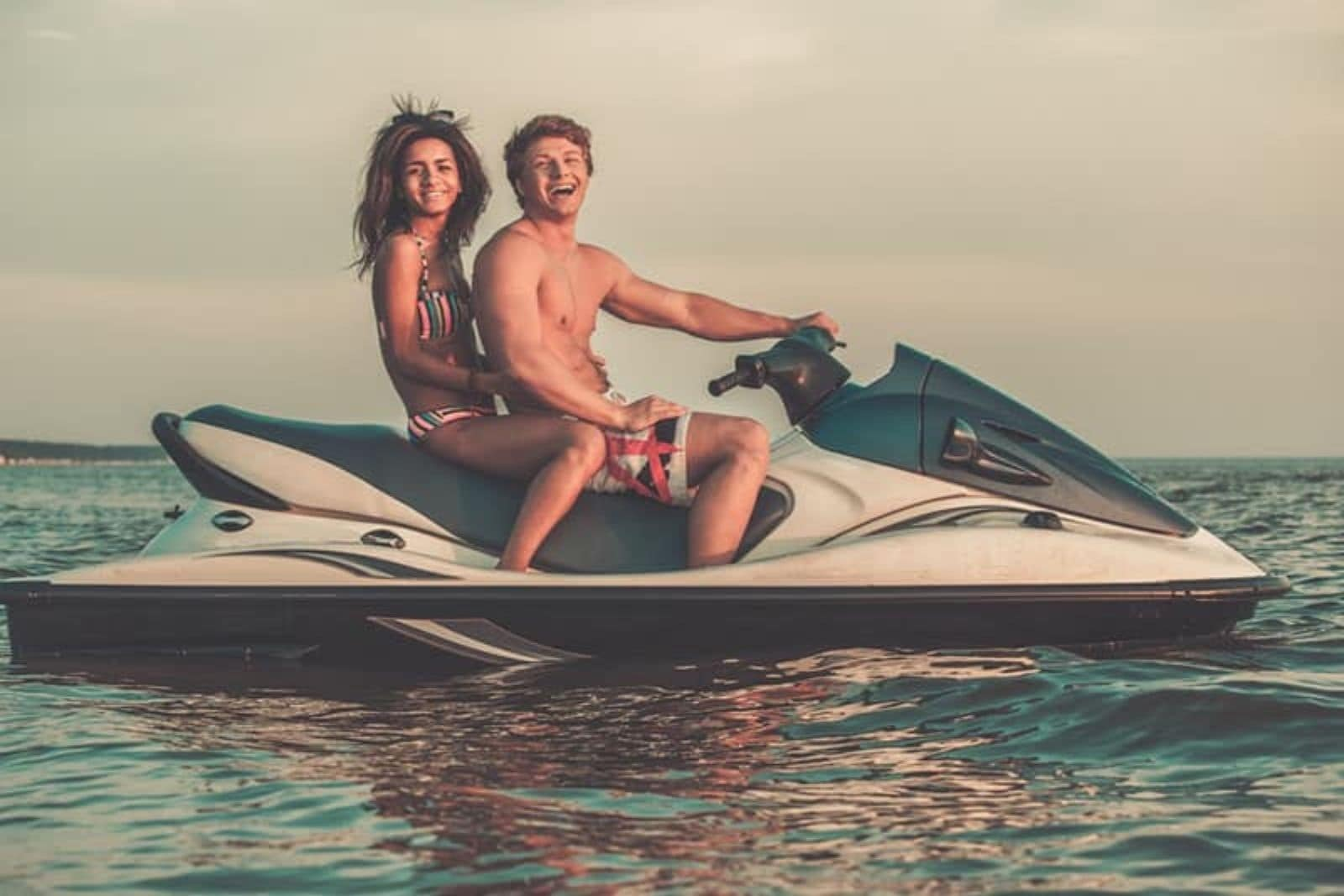 a man and a woman ride on a speedboat