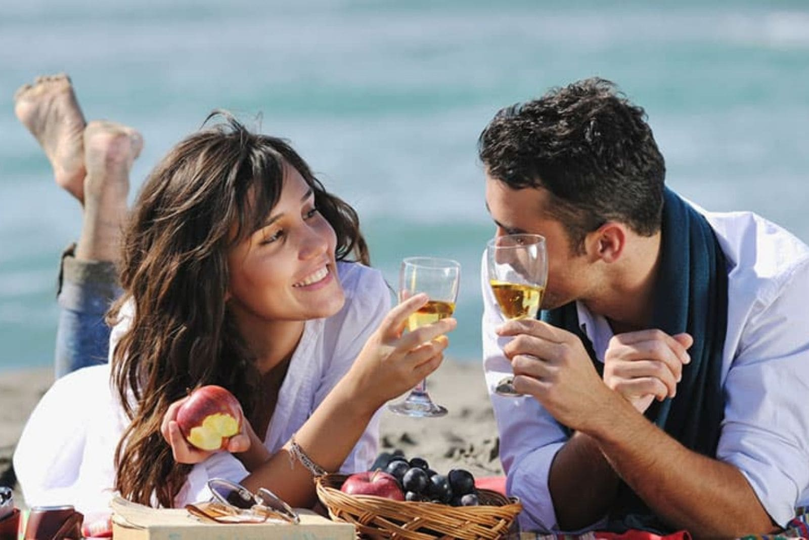 a man and a woman toast on the beach