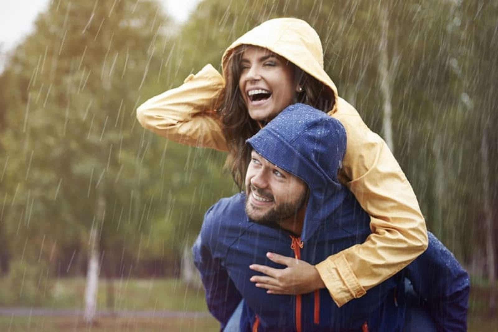 a man carries a woman in the rain