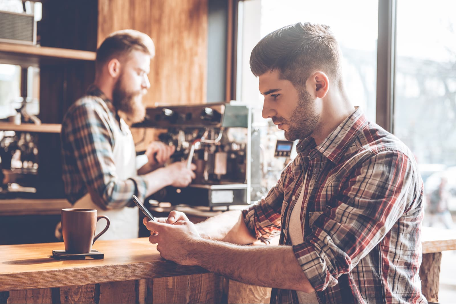 a man in a plaid shirt at the bar drinks coffee and uses a smartphone