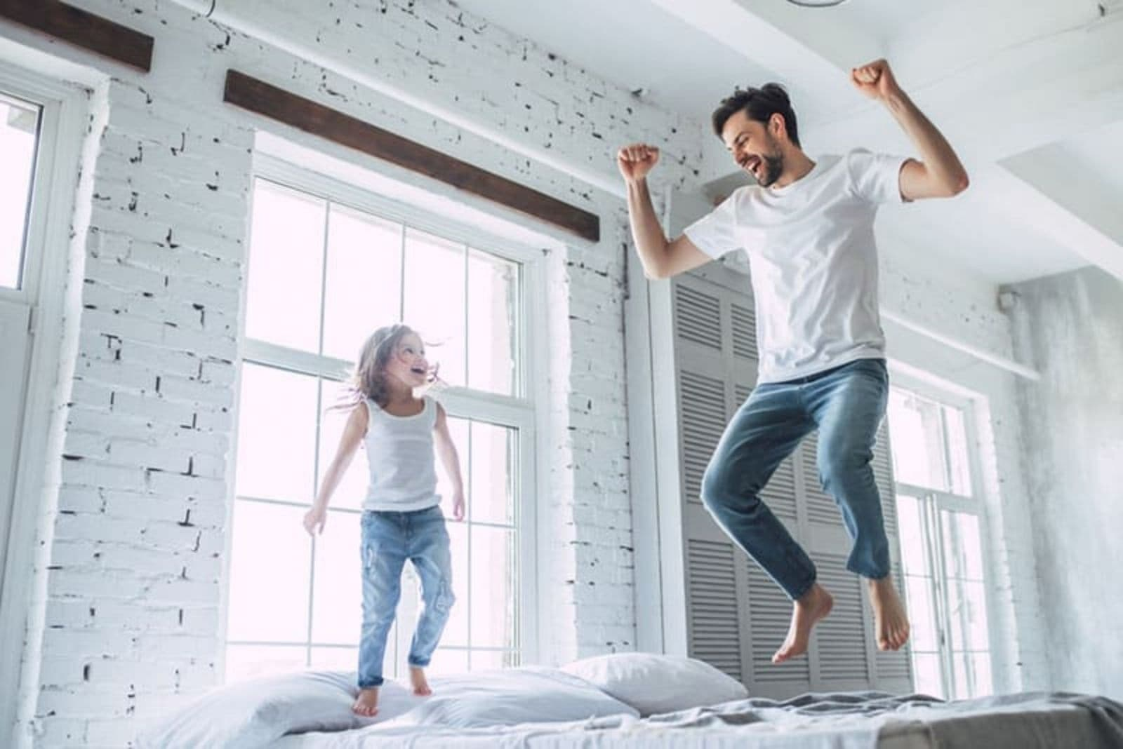 a man with a child jumps on the bed