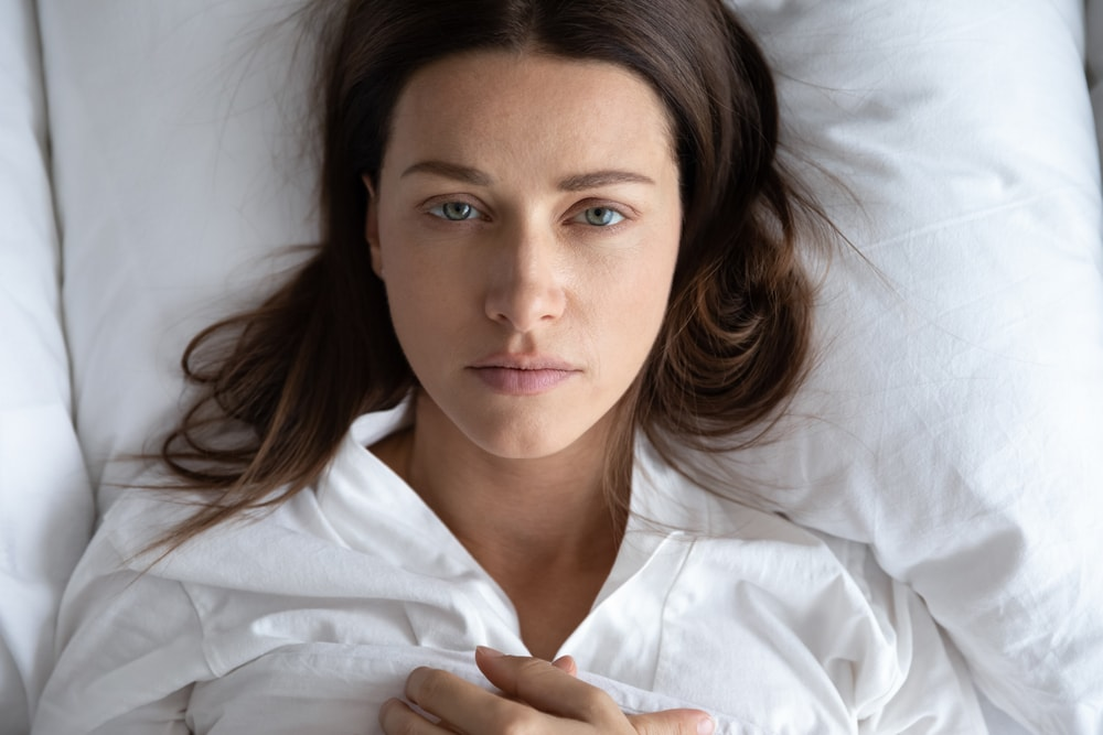 a sad brunette is lying in bed