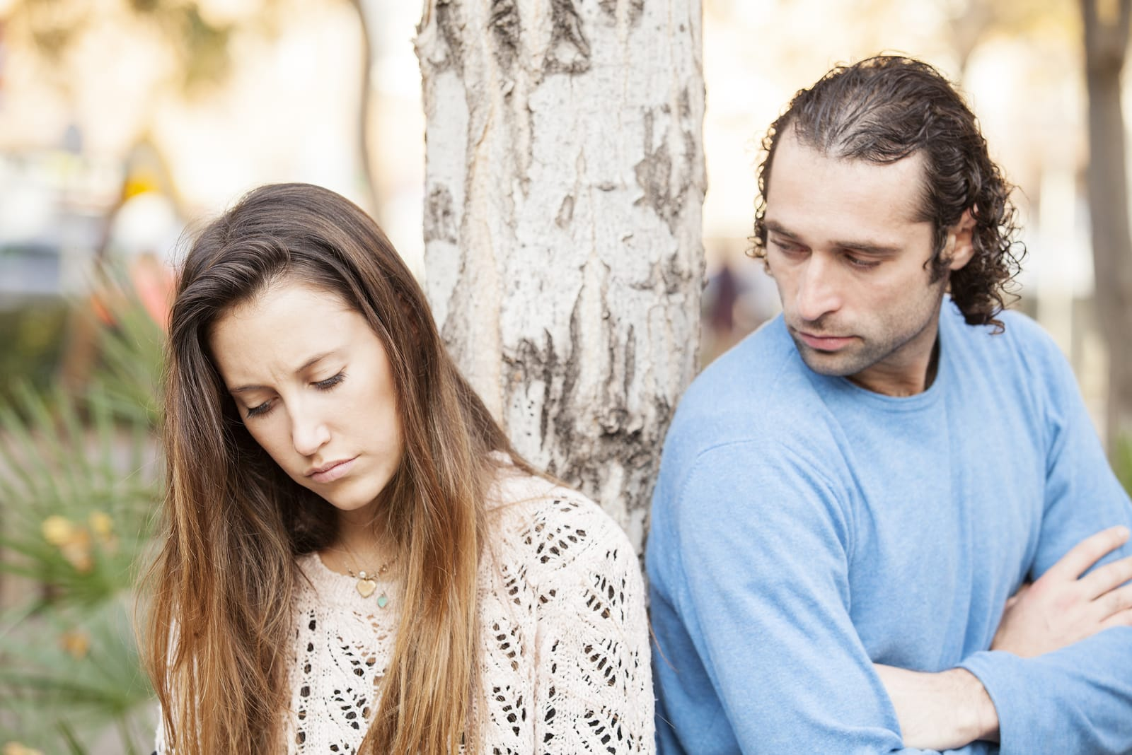 a sad loving couple standing outside by a tree