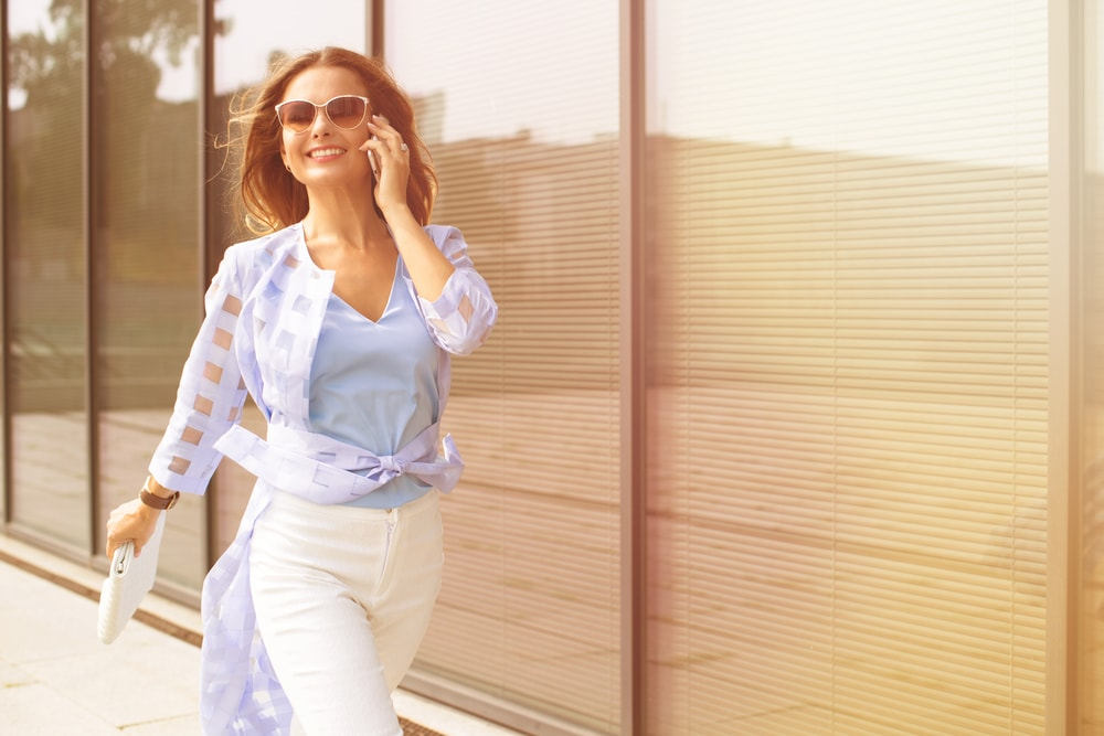 a smiling attractive woman walks down the street and talks on her cell phone