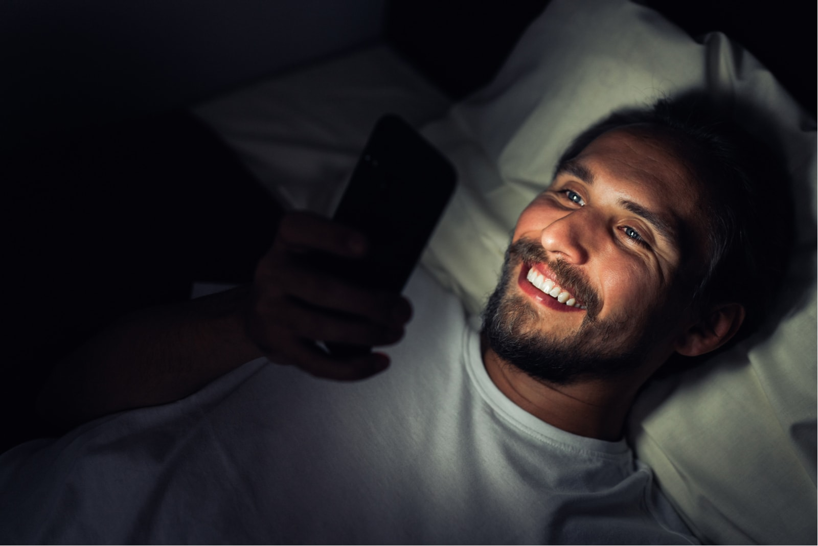 a smiling bearded man lies and reads a message on his smartphone