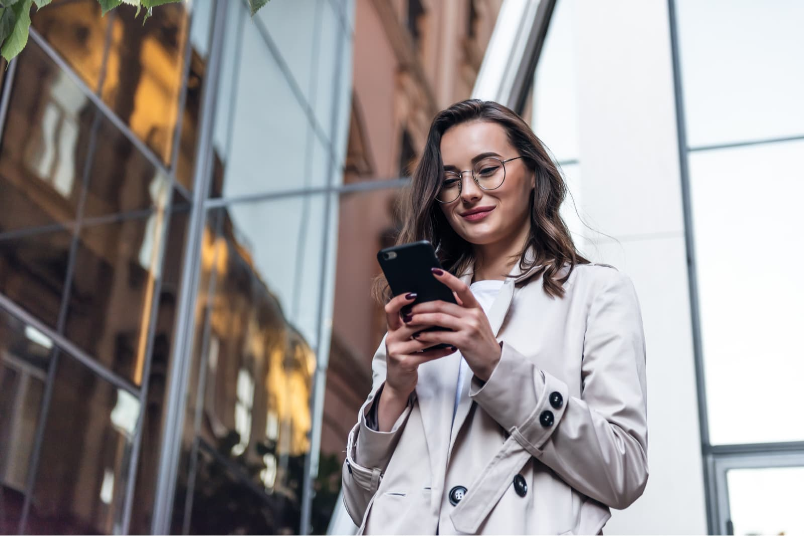 a smiling girl in a white coat stands outside and uses a smartphone