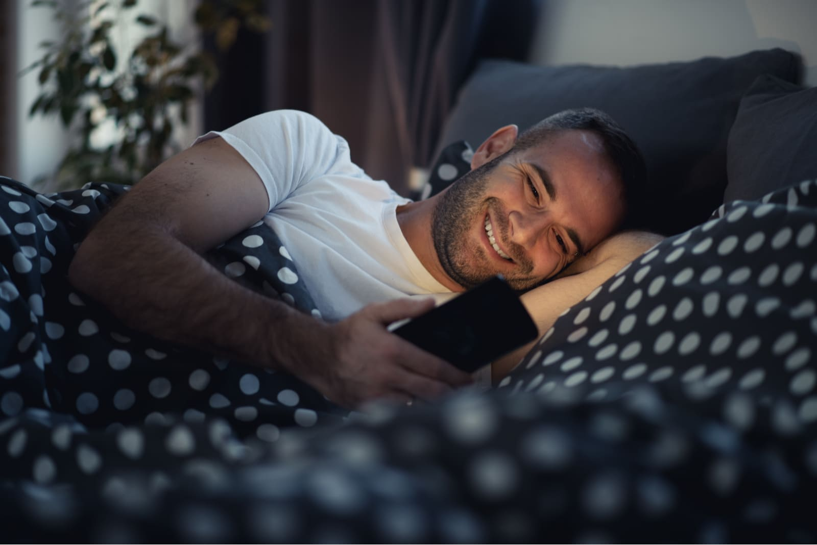 a smiling happy man lying in bed and using a smartphone