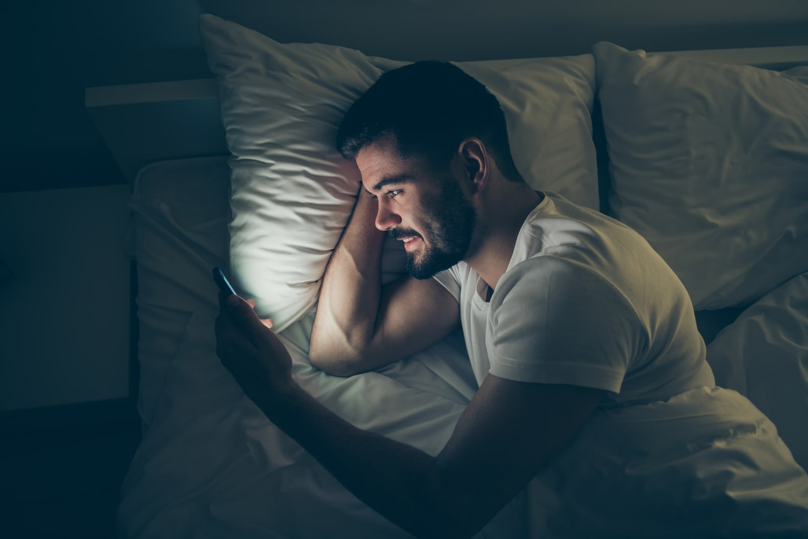 a smiling man in a white T-shirt in the evening lies in bed and watches something on his smartphone