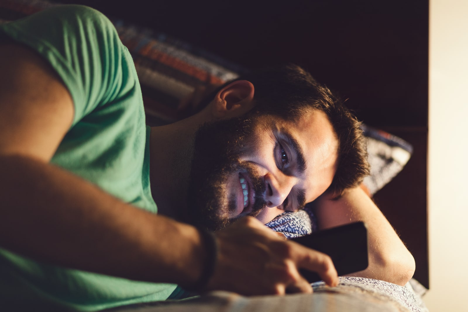 a smiling man with a beard in a green T-shirt lying in bed at night and texting