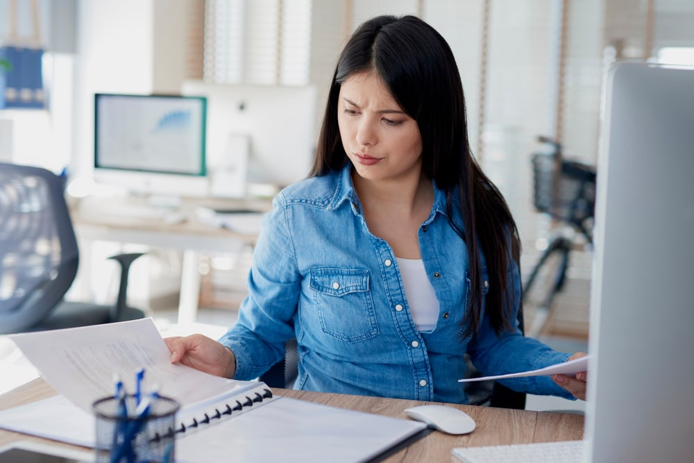 a woman is sitting at her desk reading some documents