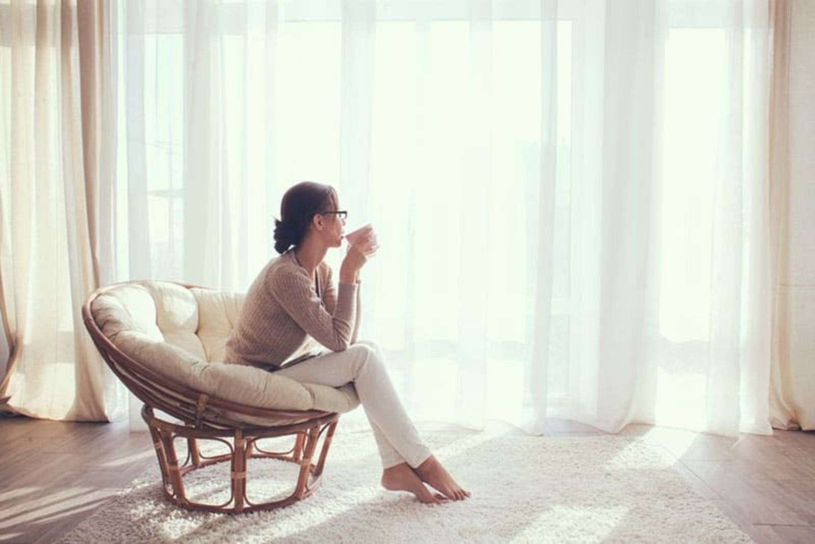 a woman sitting on a chair with a cup of coffee