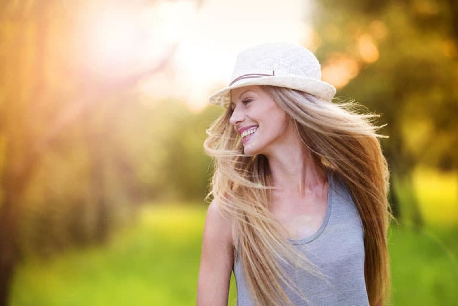 a woman with long blonde hair with a hat laughs