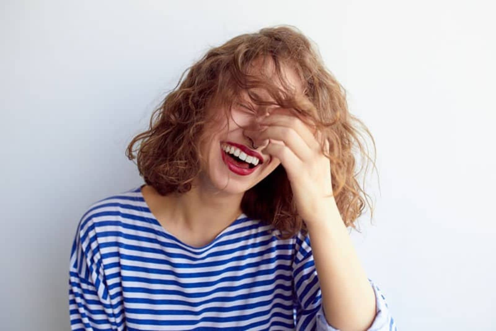 a woman with shorter brown hair laughs