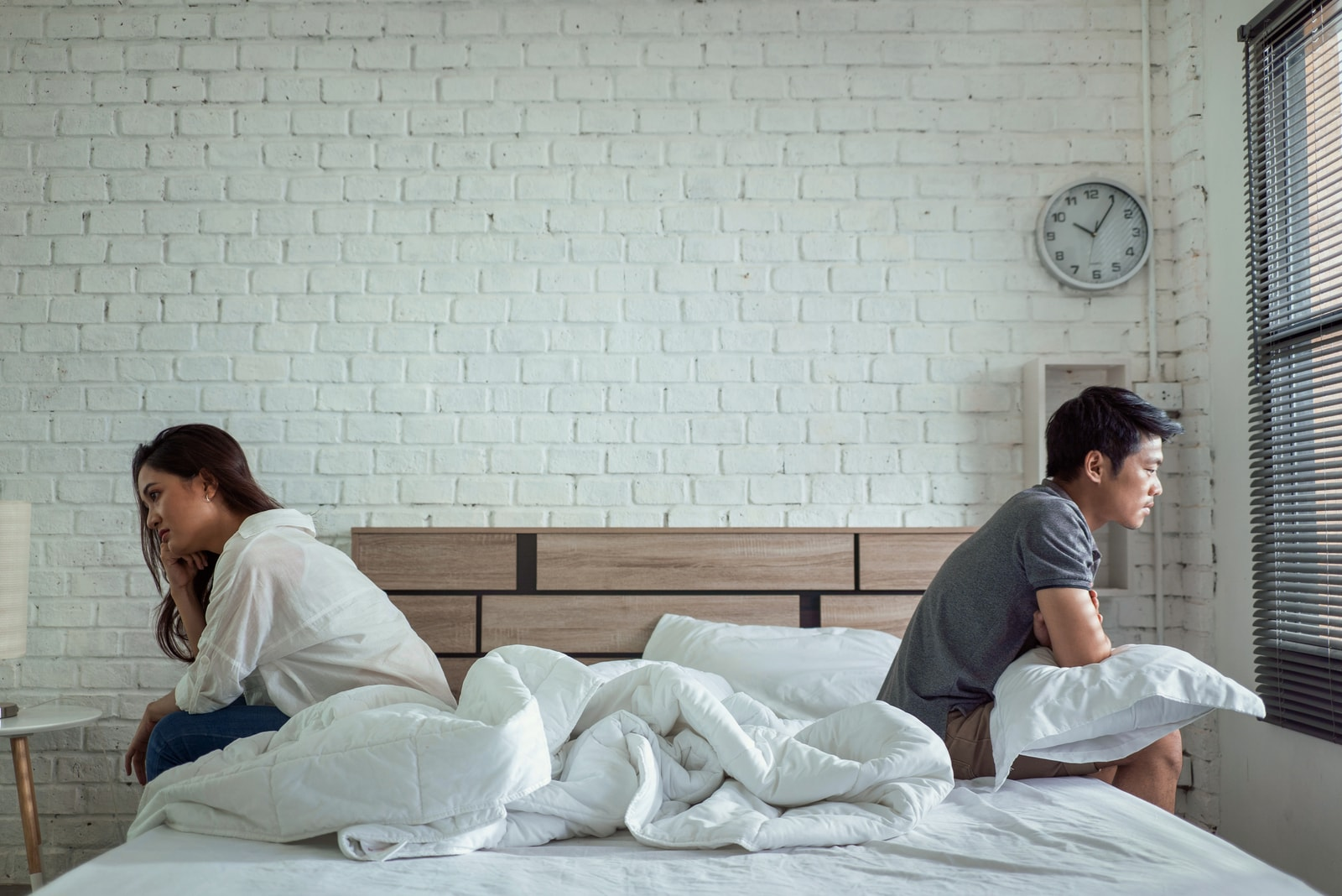 an Asian couple is sitting in bed after an argument