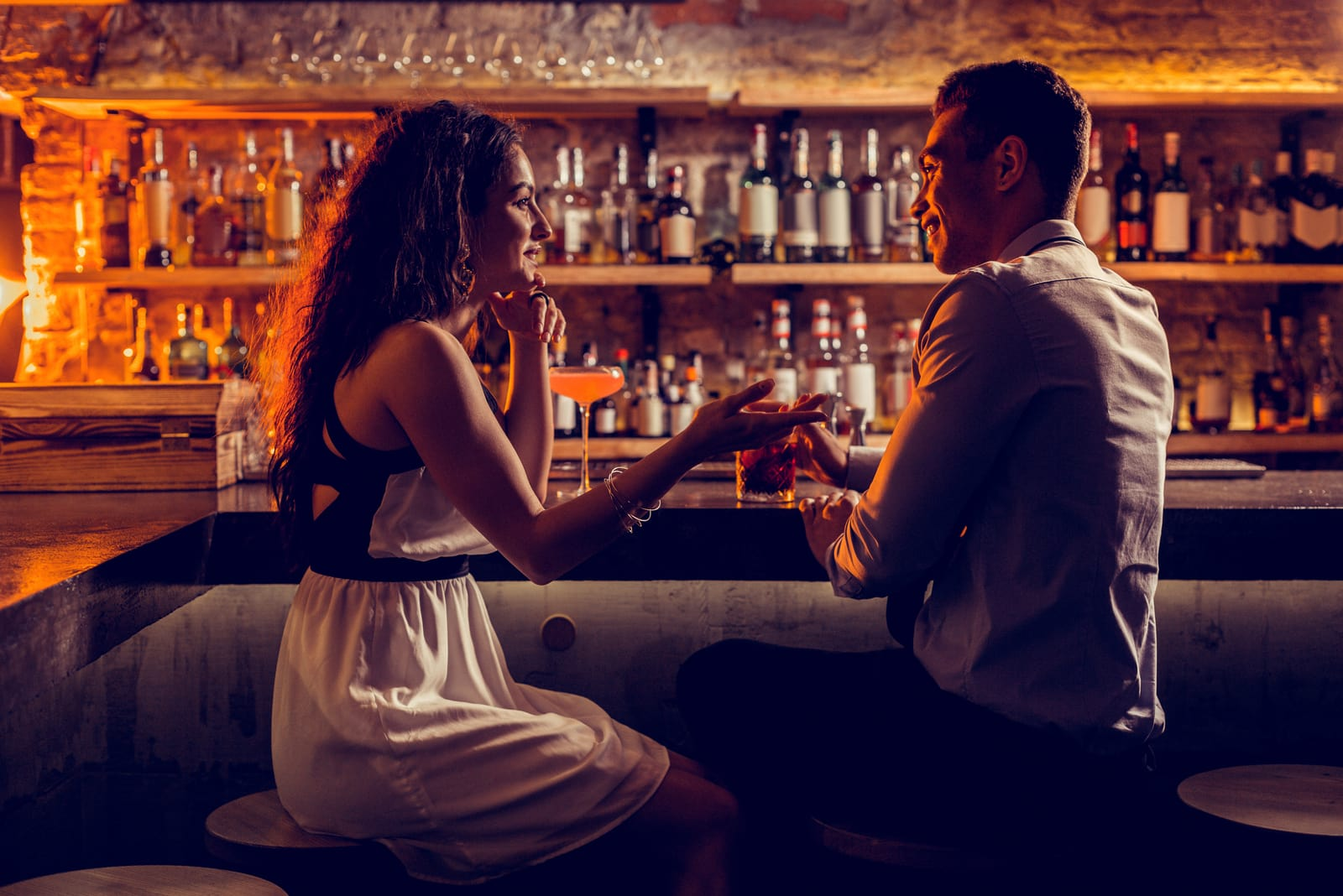 an attractive couple at the bar flirts