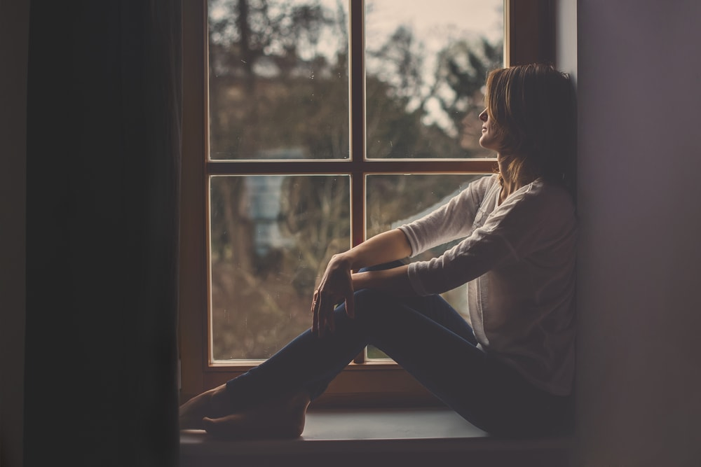 an attractive woman sits at the window and looks outside