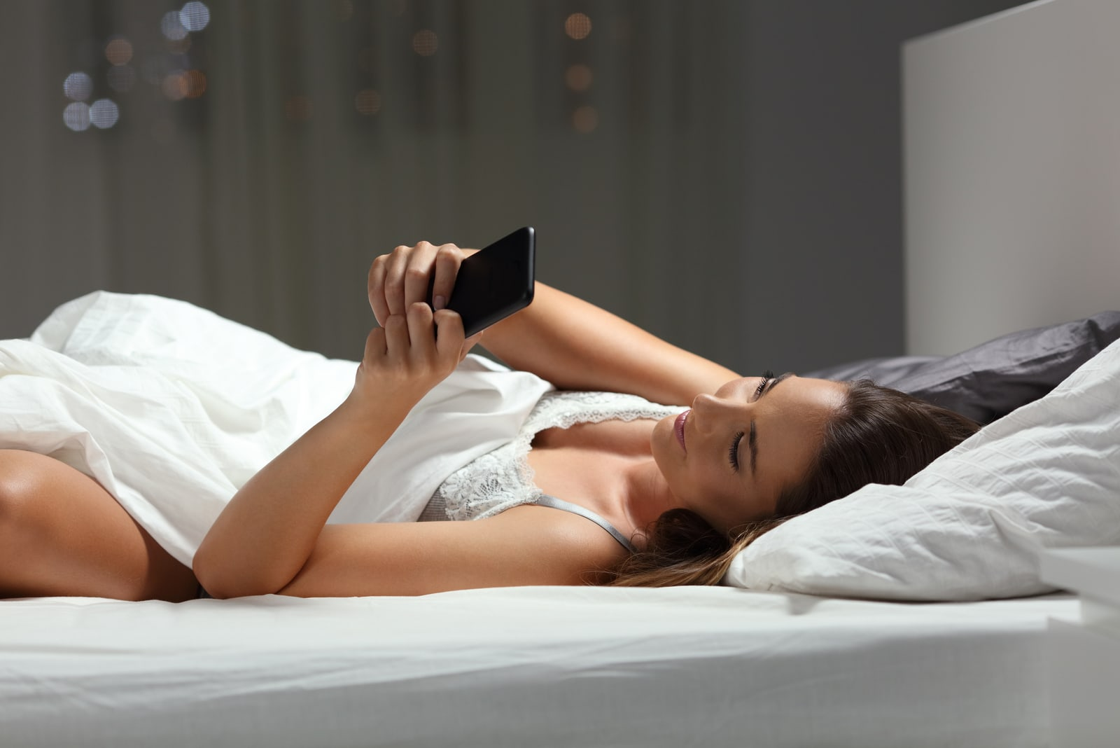 brunette lying in the bedroom bed and using a cell phone