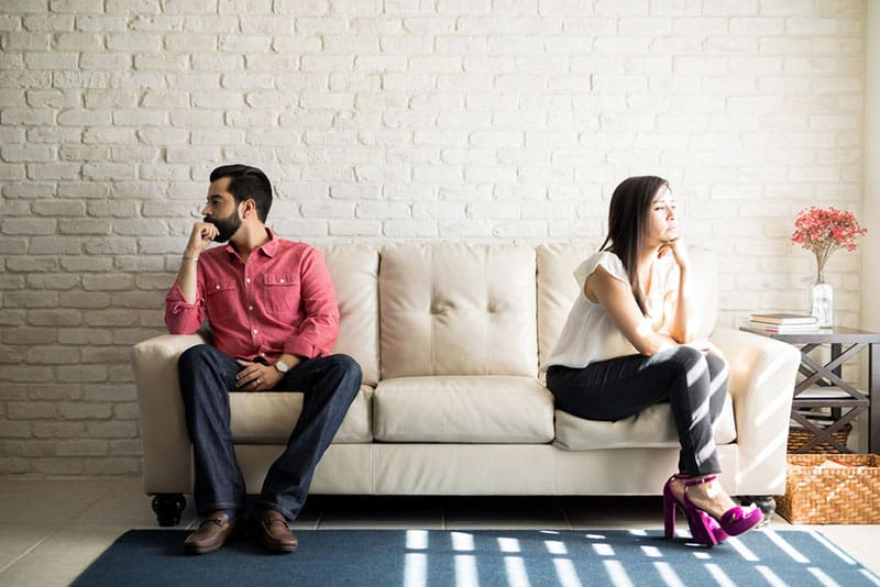 couple in argue sitting apart on the couch