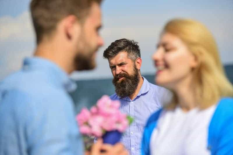 jealous man looking at couple