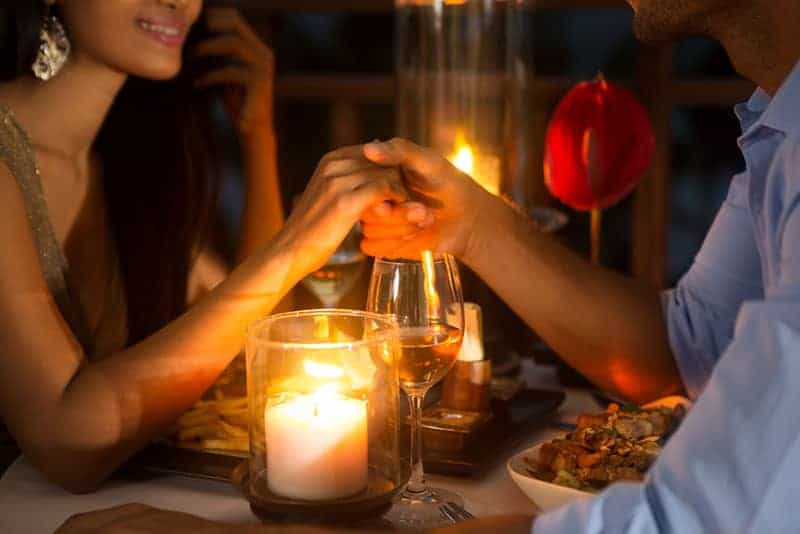 lovely couple hold hands while having a dinner date