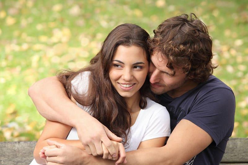 man hugging tight woman