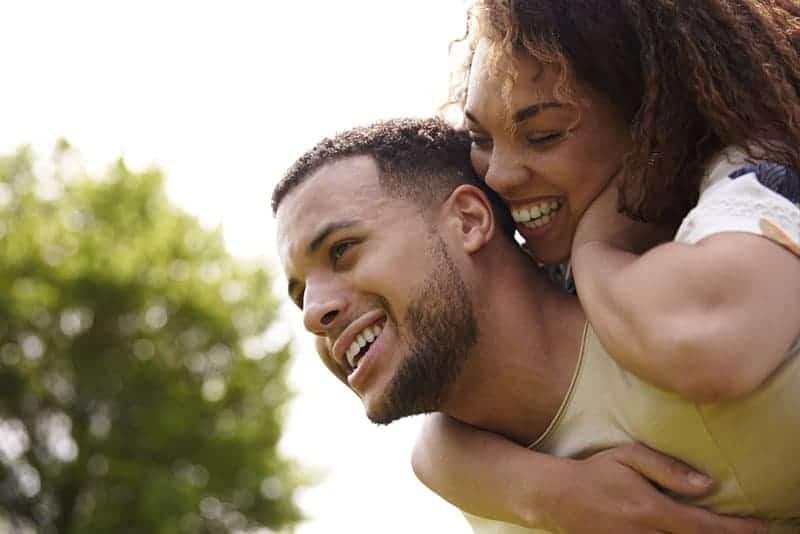 man piggybacking smiling woman