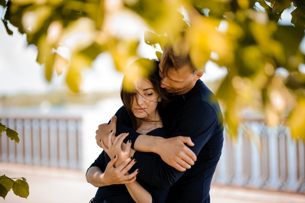 outside under a tree a man hugs a sad woman