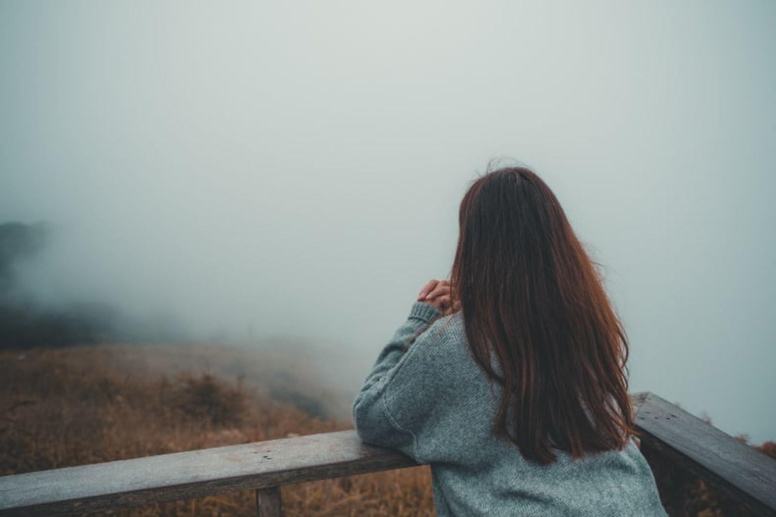 pensive sad woman looking away - foggy weather