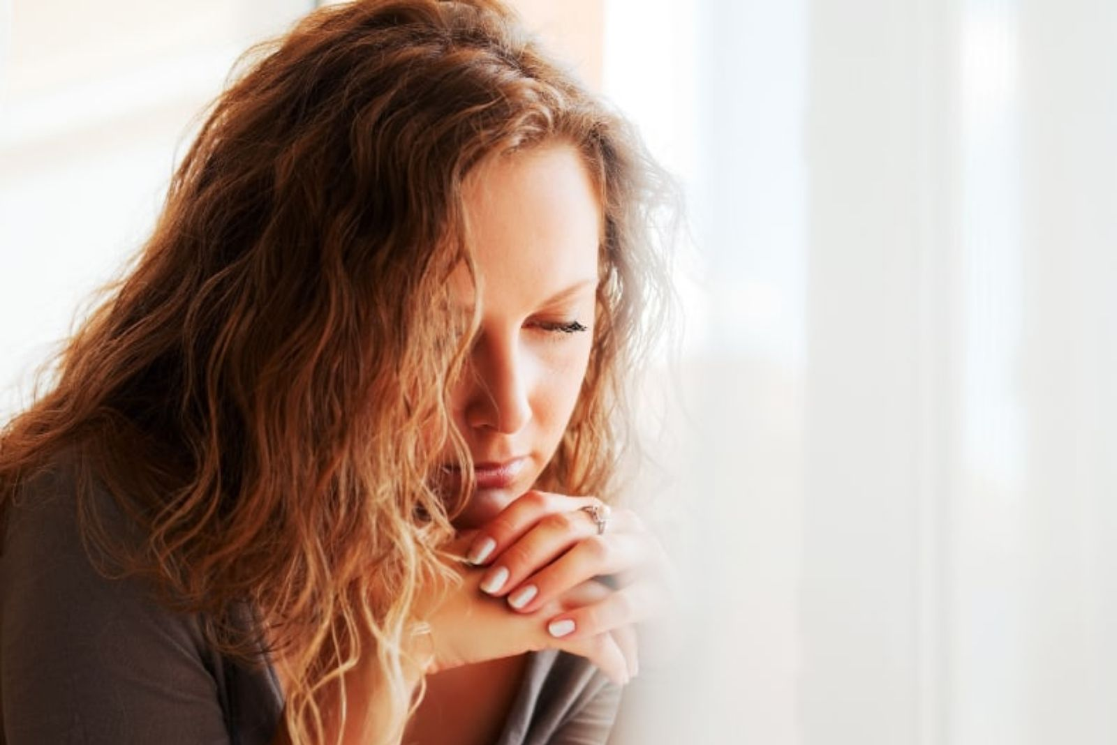 pensive woman in her house looking through the window