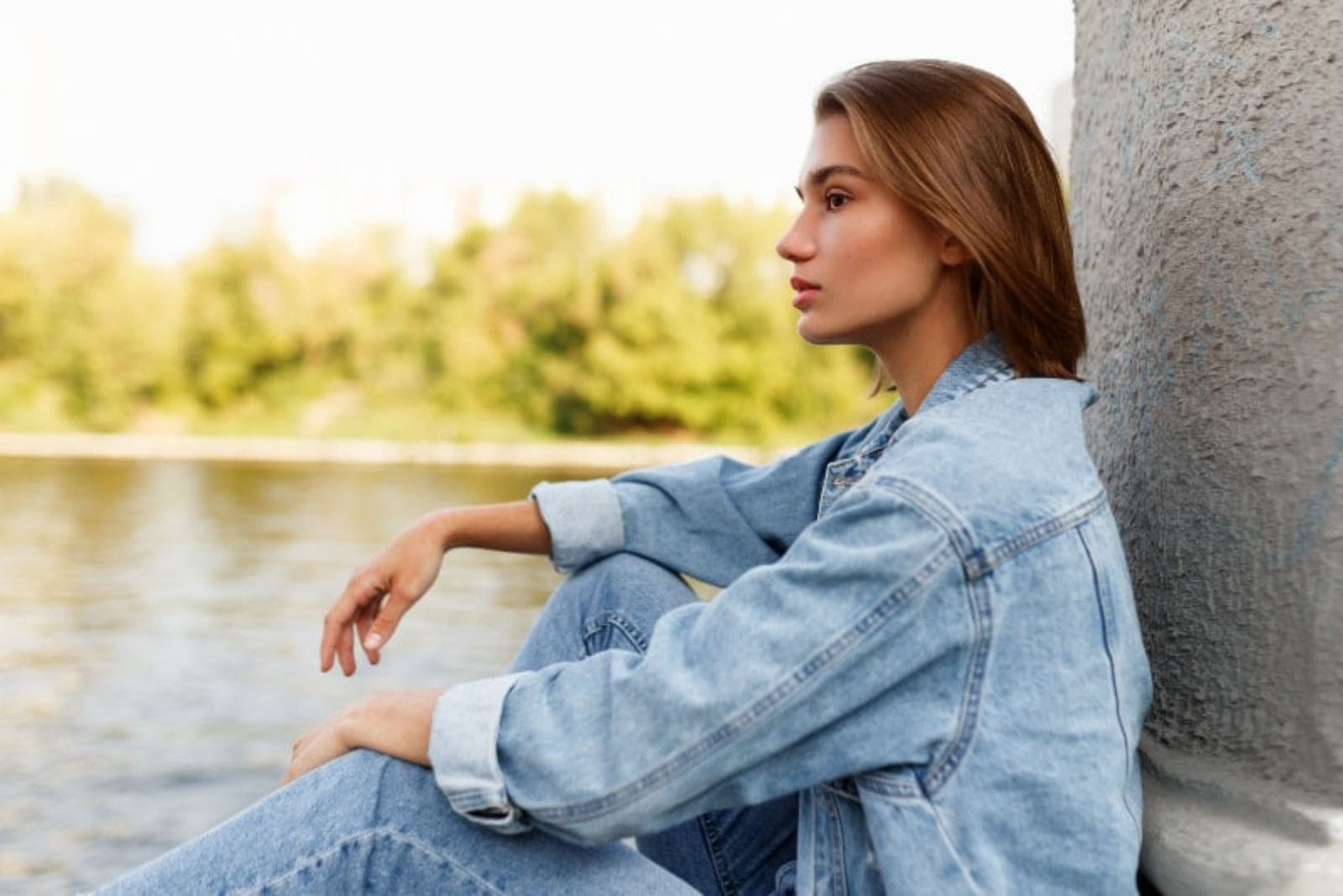 pensive woman sitting under the bridge by the river