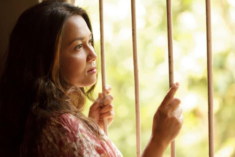 nostalgic sad woman holding window bars and looking outside