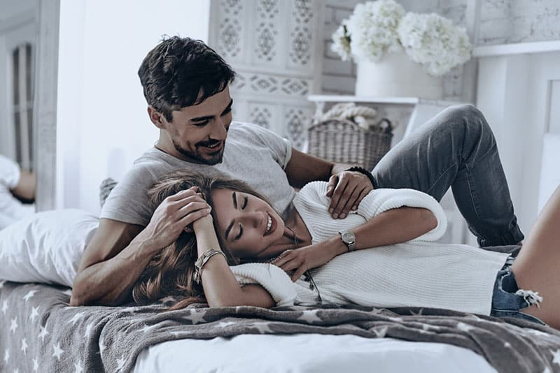 Simple joy of loving. Attractive young people lying on the bed and smiling while spending free time at home