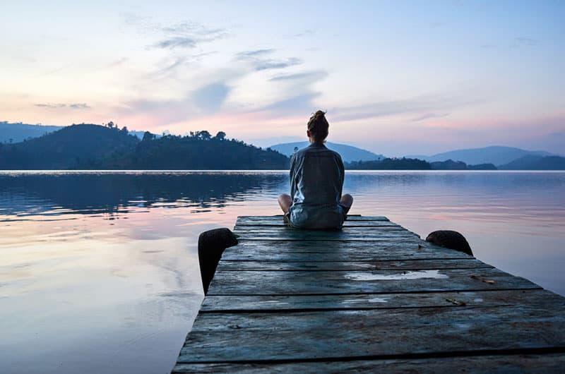 Peaceful lifestyle shot of woman sitting on dock at sunset on Lake Bunyonyi, Uganda, Africa.