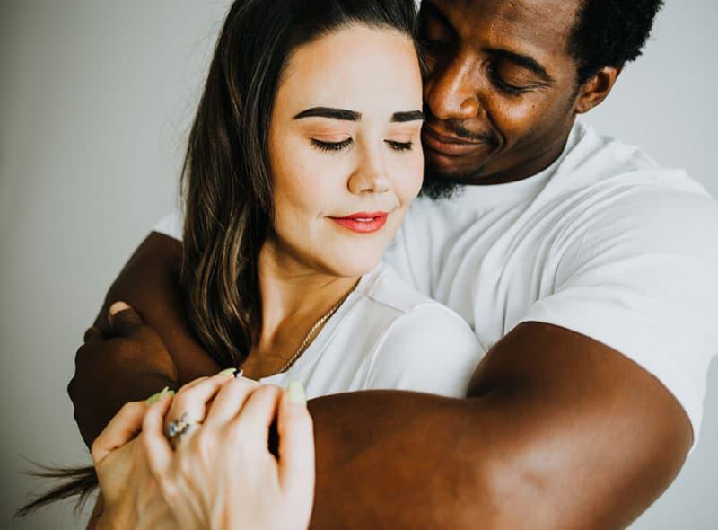 Loving Biracial Couple in Bright White Room