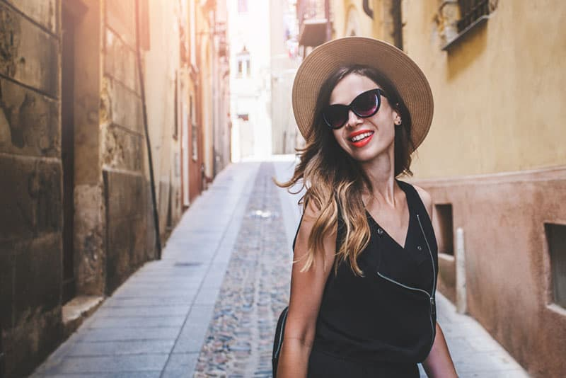 Beautiful hispter tourist girl with a backpack happy smiling walking on the european old town narrow street. Cagliari, Sardinia, Italy. Fashion blogger posing outdoors.