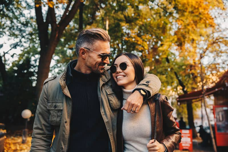 Autumn walk. Couple. Love. Man and woman in warm casual clothes are hugging and smiling while walking in the park