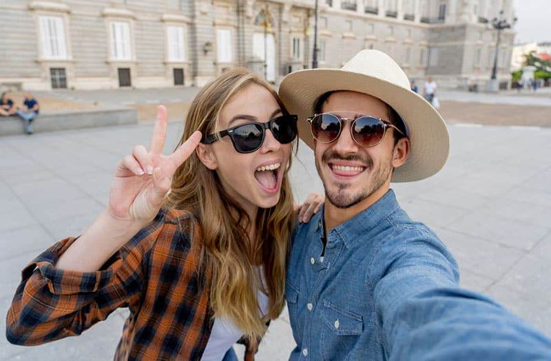 Beautiful friends tourist couple in love taking selfies at sunset while walking and visiting an European city outdoors in a romantic vacation. In Tourism, travel destination and vacation concept.