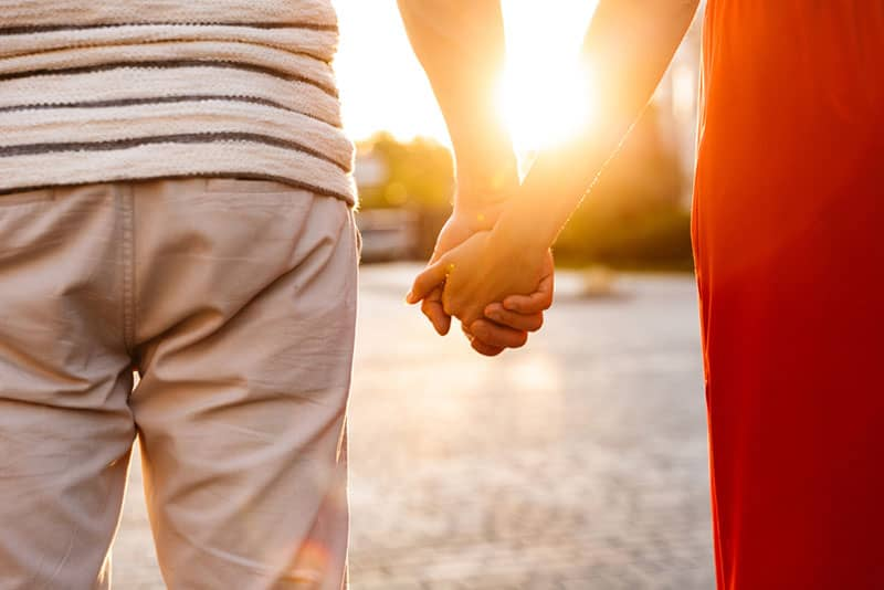 Cropped image of young caucasian couple holding hands together while walking on city street