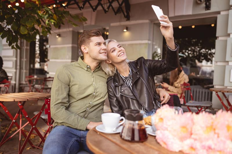 Beautiful young female taking selfie with her cheerful handsome boyfriend