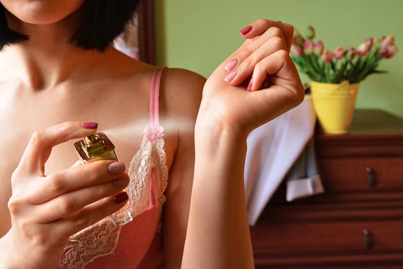 Woman puts perfume on. Perfume bottle in hand. Perfume spraying. Perfume