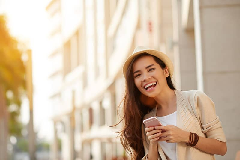 Happy young Asian woman with smartphone standing in the street