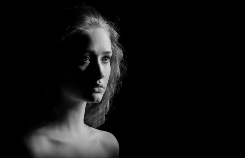 sad girl with bared shoulders looks in camera on black background, monochrome image