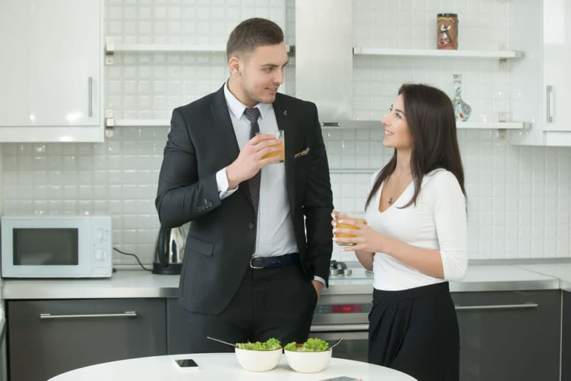 Man and woman drinking juice at the kitchen wearing formal wear, having a pleasant talk, informal conversation, maintaining good eye contact. Loving couple having breakfast before working day at home