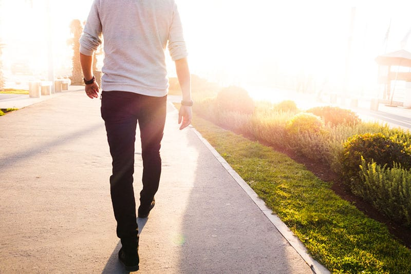 low section of a man walking in a sunny bright day