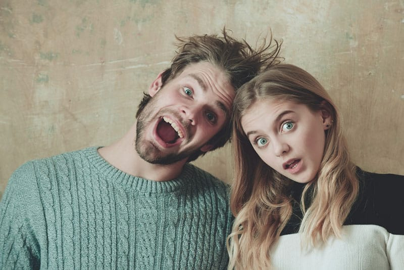 couple of friends or surprised man and woman with open mouth